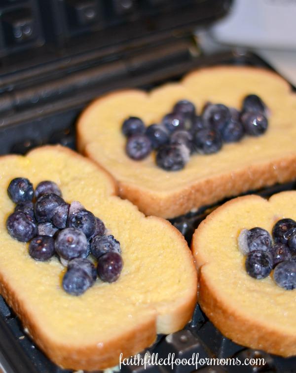 Blueberry Stuffed French Toast Waffles on waffle iron